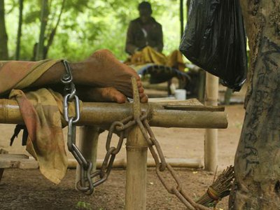 un homme au Ghana en situation de handicap mental attaché a un arbre